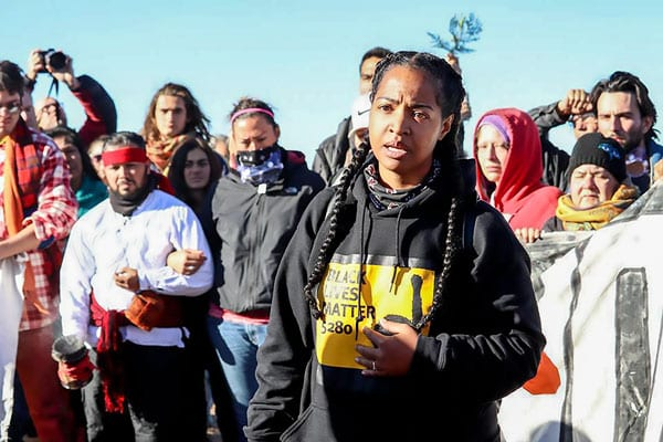 Amy E. Emery-Brown, foreground, protests alongside former CCC student Vanessa Castle, to the center left, in a bandana.