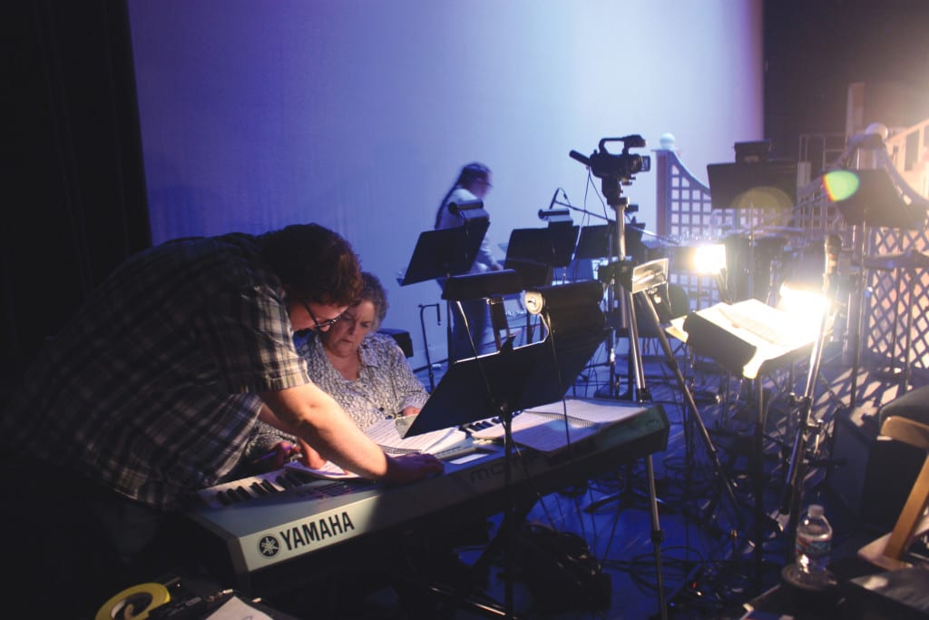 Keyboardist Susan Schroeder looks over synthesizer programming.
