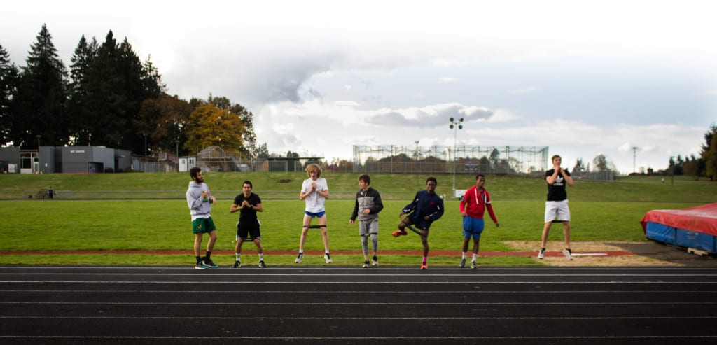 Macias, second left, does leg exercises with the cross country team.