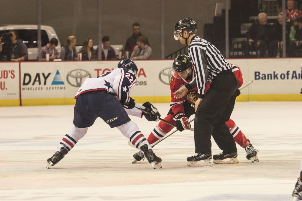 Cody Glass, for the Winterhawks, faces off against Nolan Yaremko, from Tri–City Americans.