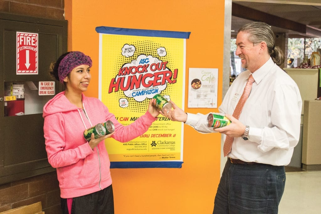 """Student Brenda Madrigal takes a few cans from the director of student leadership, John Ginsburg, to help """"knock out hunger."""""""