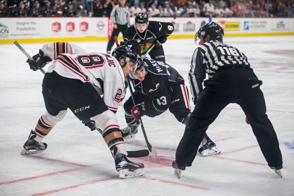 Calgary Hitmen right winger Tyler Mrkonjic (white) faces off against Portland Winterhawk left winger Skyler McKenzie (black) at the Moda Center on Nov. 12.