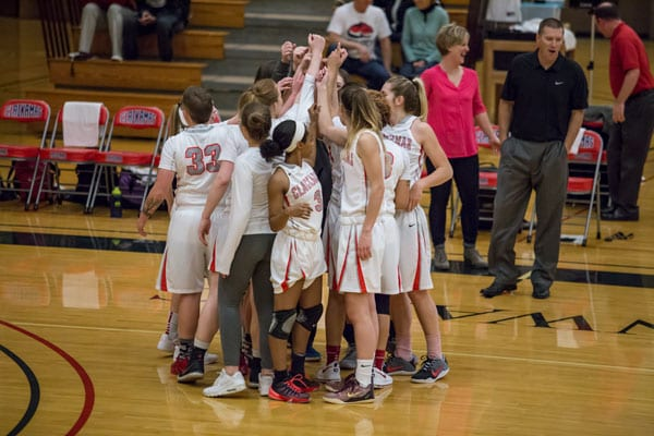 The women's basketball team huddles together before a game.